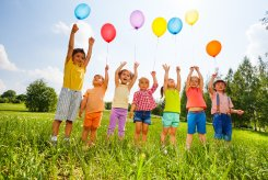 Happy kids with balloons and arms up in the sky in green field