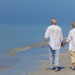 Couple de seniors se tenant la main en marchant sur la plage